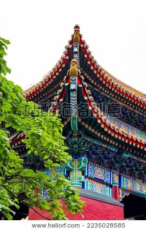 中国北京雍和宫古代建筑房顶红墙飞檐绿叶图片