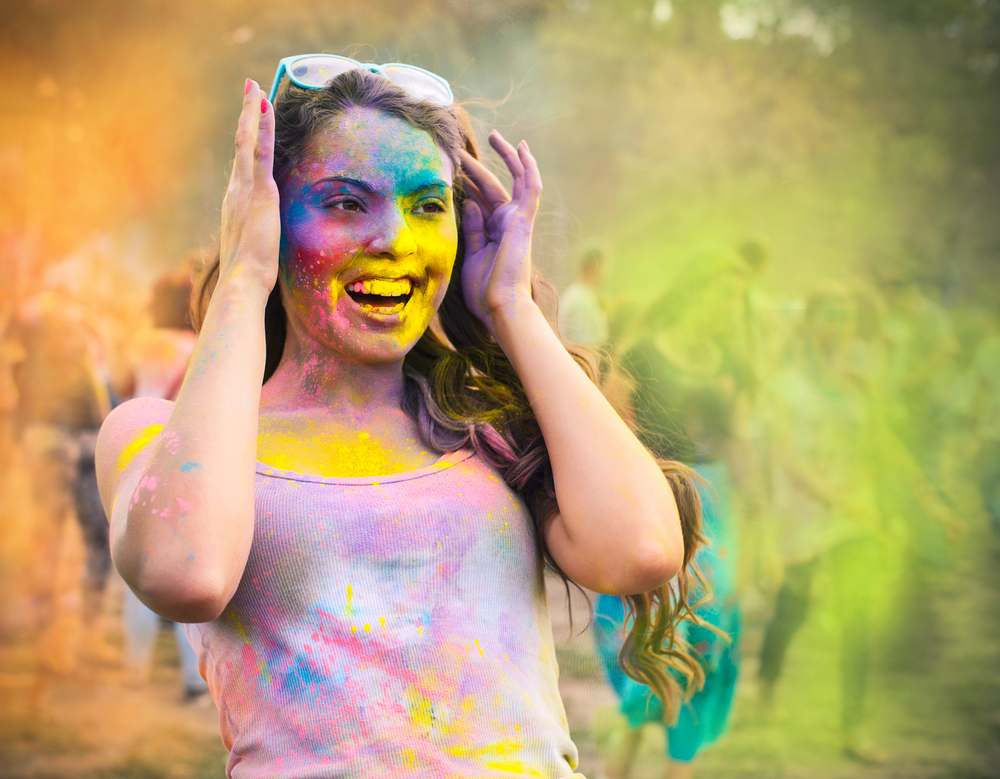 Portrait of happy young girl on holi color festival by Dasha Petrenko
