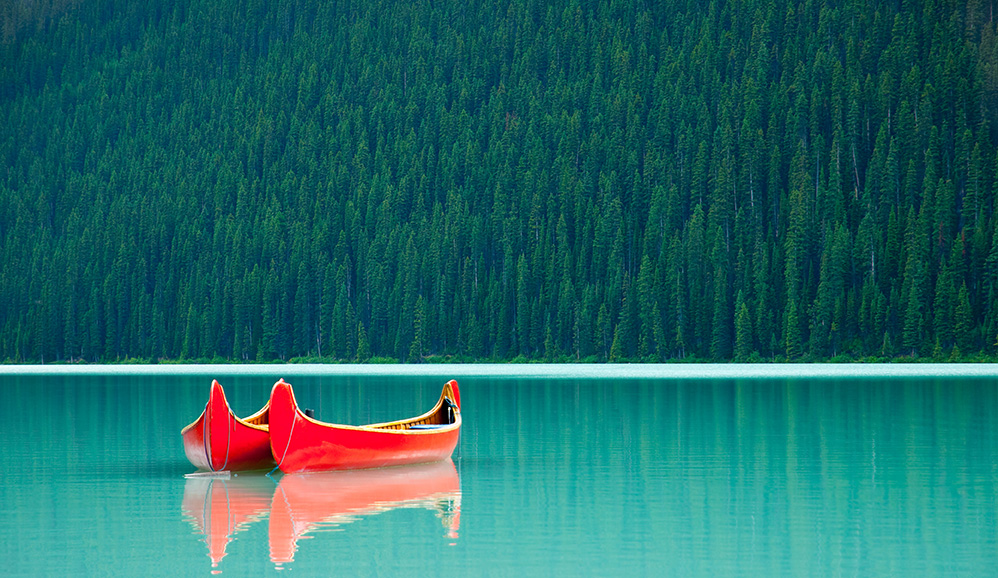 Canoes floating peacefully on the waters of Lake Louise, Banff National Park, Alberta, Canada by Darren J. Bradley